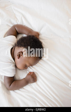 Overhead view of Black baby boy sleeping on bed - Stock Photo