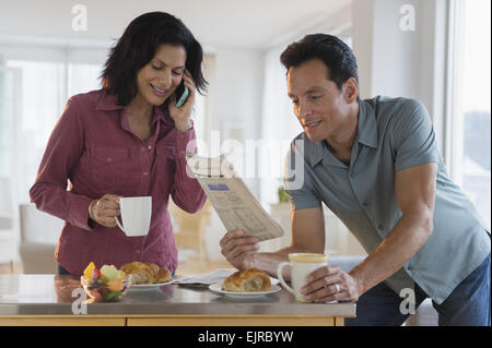 Couple reading newspaper and talking on cell phone at breakfast - Stock Photo