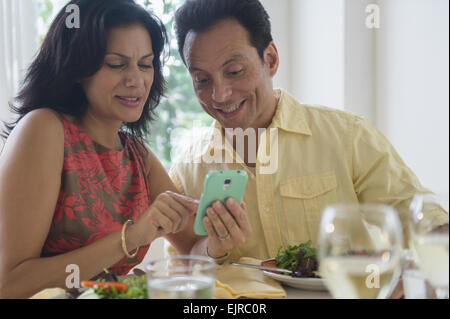 Couple using cell phone in restaurant - Stock Photo