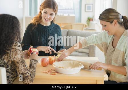 Women baking pie in kitchen - Stock Photo