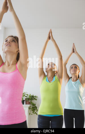 Women practicing yoga in class - Stock Photo