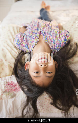 Smiling Vietnamese girl laying on bed - Stock Photo