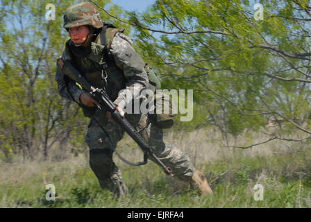 U.S. Army Pfc. Gabriella Ravensborg, of the 344th Military Intelligence Battallion, runs for cover during a field - Stock Photo