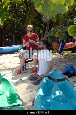 Willow and Chris Fesmire wait to take a sit-on-top kayak out for a spin off shore of Cinnamon Bay, St. John, U.S. - Stock Photo