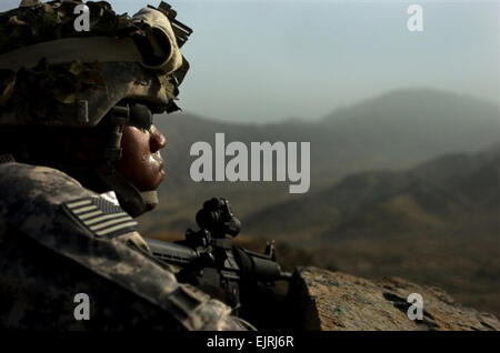 Spc. Rufino Persaud, a native of Jacksonville, Fla., watches over the   Afghan countryside while fellow members - Stock Photo