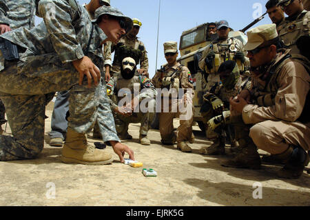 U.S. and Iraqi Soldiers gather around for an after-action review with after an improvised explosive device reaction - Stock Photo