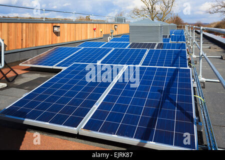 Row of photovoltaic cells on roof of modern  college building - Stock Photo