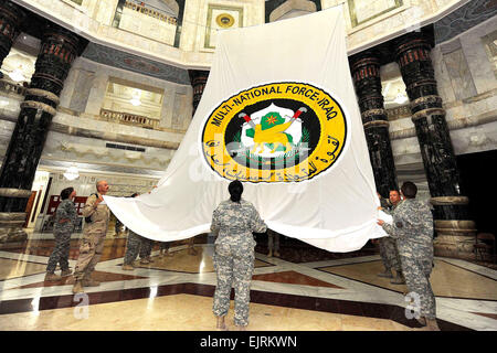 Military members of Multi-National Force Iraq straighten out an enormous flag in preparation for the change of command - Stock Photo
