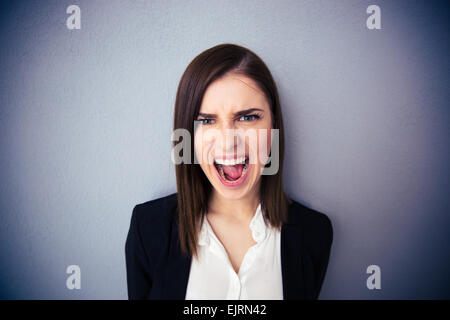 Angry businesswoman shouting over gray background. Looking at camera - Stock Photo