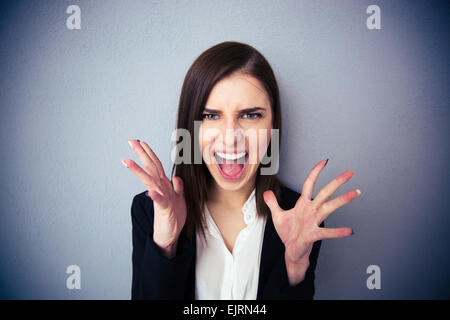 Angry woman screaming over gray background. Looking at camera - Stock Photo