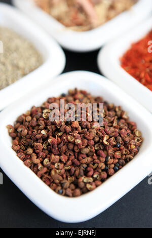 Szechuan peppercorns with, clockwise from the peppercorns, cumin seeds, lemongrass and saffron in white dishes - Stock Photo