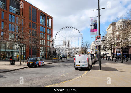 Manchester, UK: Manchester City Centre and the Big Wheel in Picadilly Gardens. - Stock Photo