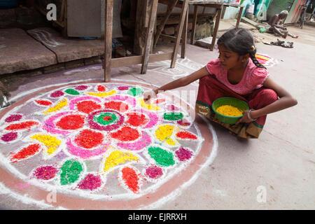 Girl creating a rangoli to celebrate the Pongal festival in Kumbakonam - Stock Photo