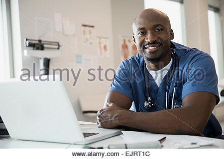 Portrait of smiling doctor in scrubs in clinic - Stock Photo