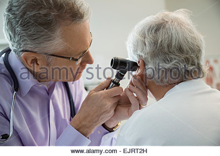 Doctor checking senior mans ears with otoscope - Stock Photo