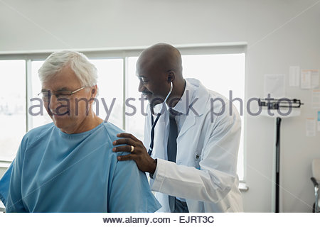 Doctor checking senior mans back in examination room - Stock Photo