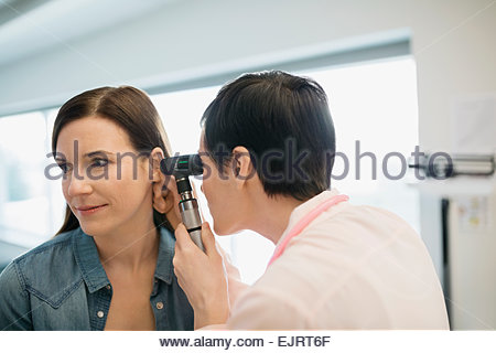 Doctor checking patients ears with otoscope - Stock Photo