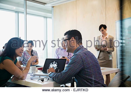 Doctors discussing CT scan in hospital conference room - Stock Photo