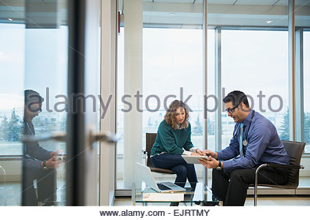 Doctor and patient consulting with digital tablet - Stock Photo