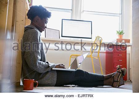 Architect working on laptop on floor - Stock Photo