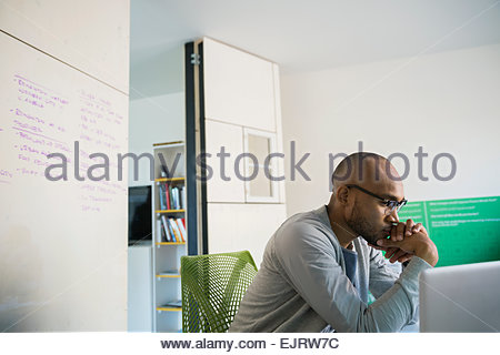 Serious businessman working at laptop in office - Stock Photo