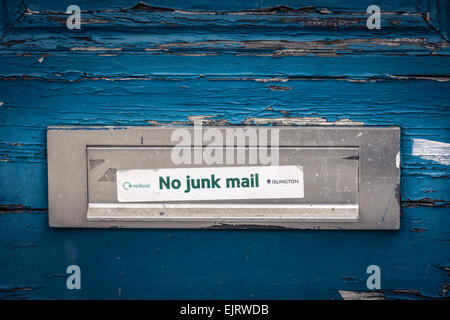 A Letterbox on a weathered door in North London with a 'No Junk Mail' sticker. - Stock Photo