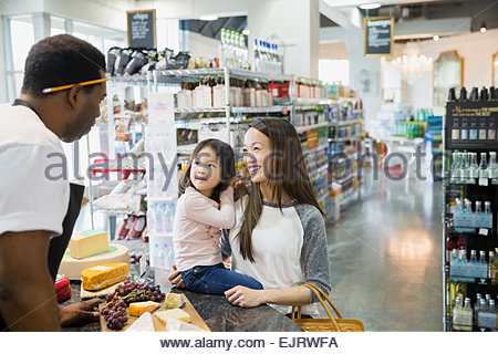 Mother and daughter talking to cheese counter worker - Stock Photo