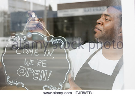 Proud business owner flipping open sign - Stock Photo