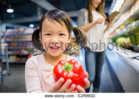 Portrait of smiling girl holding red bell pepper - Stock Photo