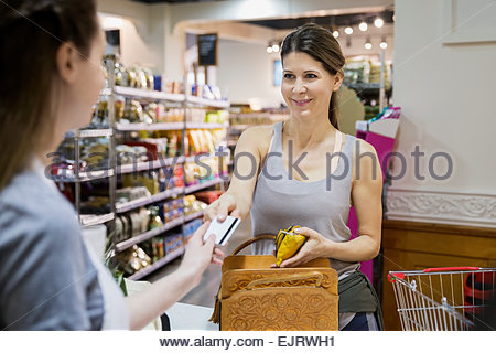 Woman paying at grocery store checkout - Stock Photo