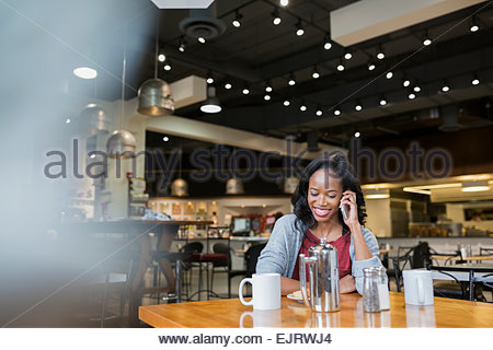 Smiling woman talking on cell phone in cafe - Stock Photo