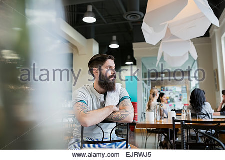 Pensive bearded worker in cafe - Stock Photo