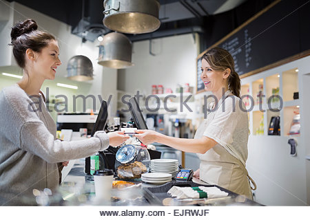 Woman paying at cafe counter - Stock Photo