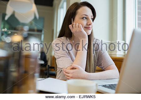 Smiling woman looking away at laptop in cafe - Stock Photo