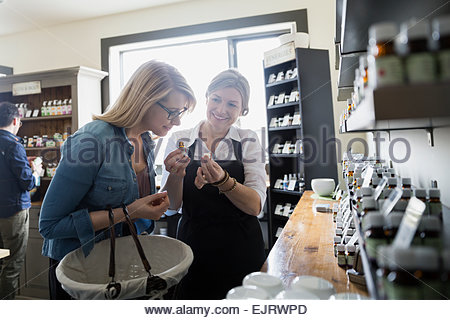 Apothecary shop owner showing woman essential oils - Stock Photo