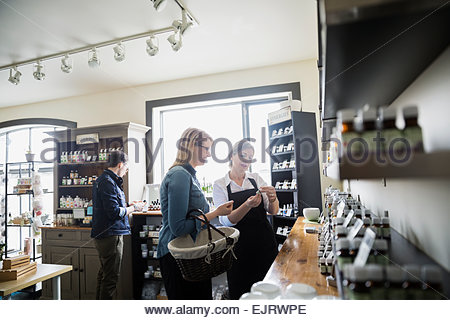 Apothecary shop owner helping woman - Stock Photo