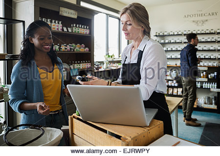 Apothecary shop owner showing woman product - Stock Photo