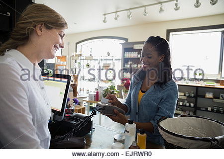 Woman paying with credit card in apothecary shop - Stock Photo