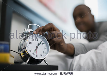 Man awaking to and turning off alarm clock - Stock Photo