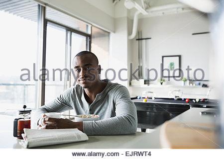Portrait of man enjoying morning breakfast in kitchen - Stock Photo