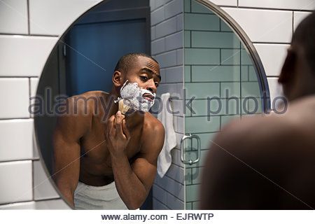 Bare chested man shaving face in bathroom mirror - Stock Photo