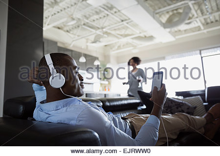 Man with headphones using cell phone on sofa - Stock Photo