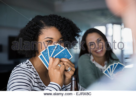 Woman hiding behind playing cards - Stock Photo