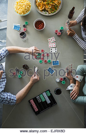 Overhead view of friends playing poker - Stock Photo