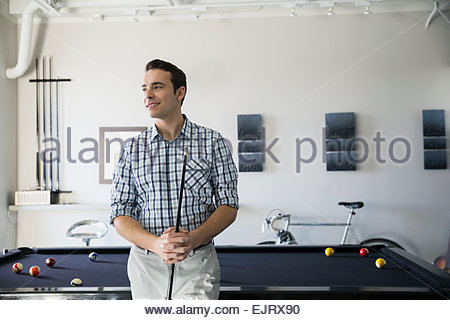 Smiling man playing pool and looking away - Stock Photo