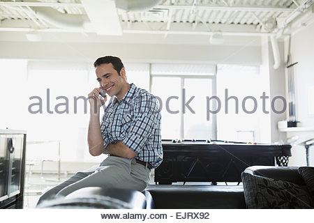 Smiling man talking on cell phone living room - Stock Photo