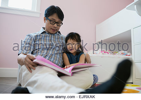 Grandfather reading book to granddaughter in bedroom - Stock Photo