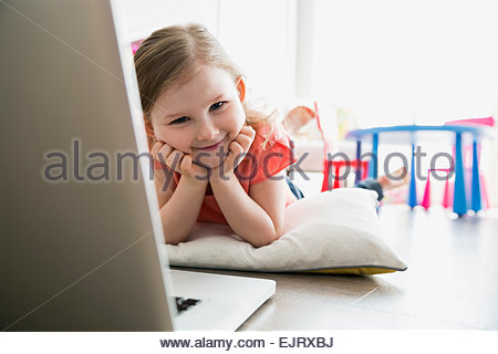 Portrait of smiling girl on floor with laptop - Stock Photo