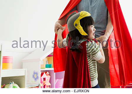 Father and daughter in cape costumes dancing - Stock Photo