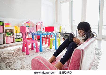 Girl using digital tablet on sofa in playroom - Stock Photo